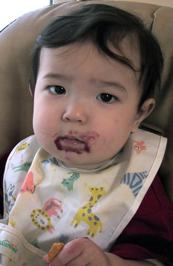 11-month-old Anthony with   blueberry-apple babyfood all over his face