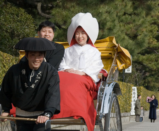Newly-married Japanese couple in traditional dress riding in a rickshaw next to the Heian Shrine, Kyoto Japan