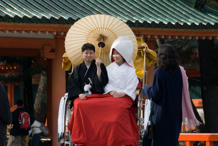 Newly-married Japanese couple in traditional dress, riding in a rickshaw, posing for pictures in front of the Heian Shrine, Kyoto Japan