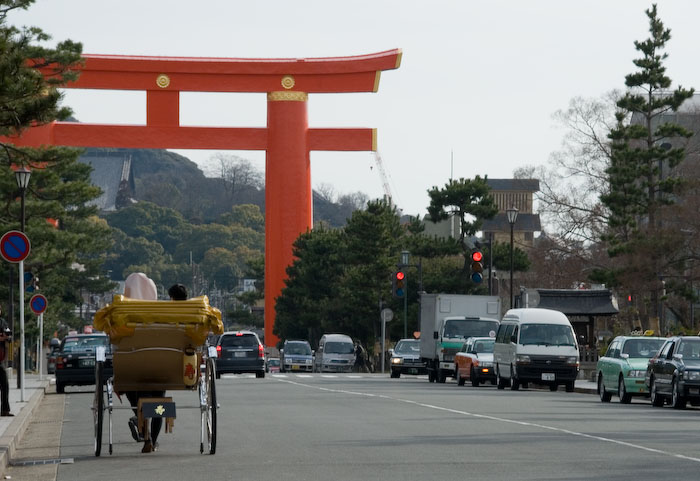 Rickshaw on the streets of Kyoto, Japan, in front of the main 'Torii' gate of the Heian Shrine