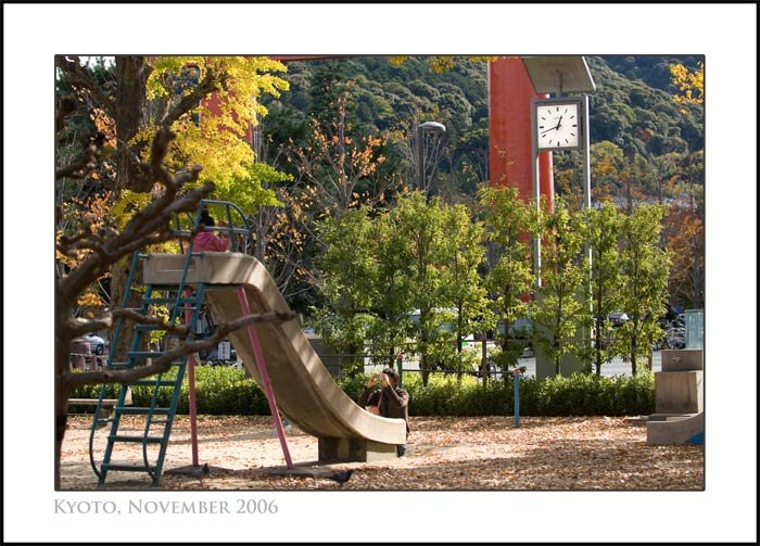 A man photographs his young child in a park in Kyoto, Japan, as the leaves just start to change to autumn colors