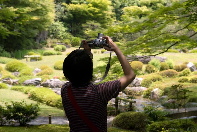A silhouetted Verena Wee photographs leaves at Murin-An, Kyoto Japan