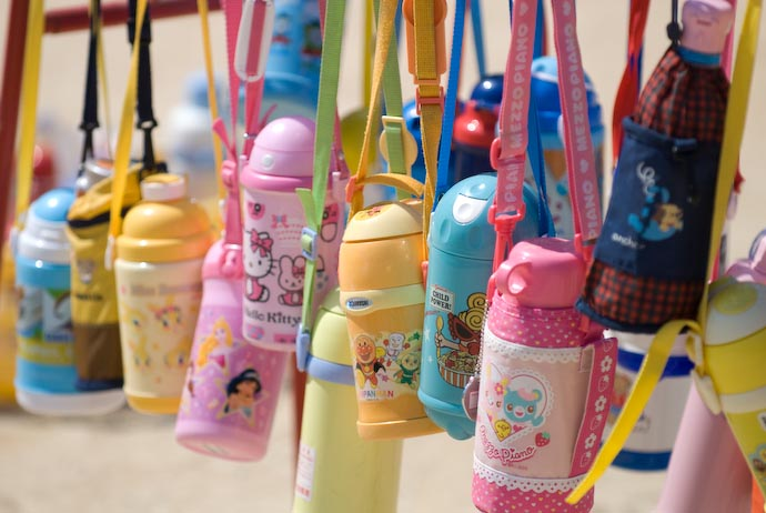 Racks of colorful kids' thermos bottles await their owner at a preschool Sports Day