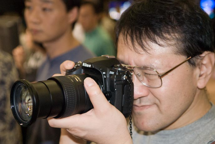 Shimada-san Tries the Nikon D300 With Nikkor 18 -200VR -- Osaka, Japan -- Copyright 2007 Jeffrey Eric Francis Friedl