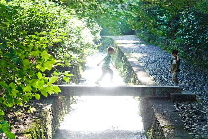 Sun Hitting the Water as Gen crosses the small stone bridge ( Gen's dad also snapped a shot at the exact same moment ) -- Otsu, Shiga, Japan -- Copyright 2008 Jeffrey Eric Francis Friedl, http://regex.info/blog/