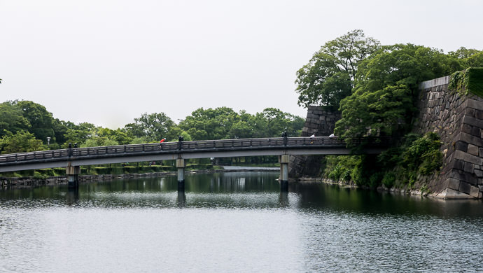 Crossing the Moat the dots on the bridge are Gorm, Manseki, and Michael ( another dot and a building in the background were removed in post ) -- Osaka Castle (大阪城) -- Osaka, Japan -- Copyright 2015 Jeffrey Friedl, http://regex.info/blog/