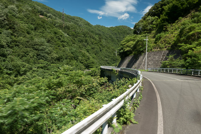 Supersteep too steep even for the road to be cut into the mountain, the road is a ledge wrapping around the mountain 10:06 am (from start: 5h 42m / 73 km / 45.2 miles) taken while cycling at 39 kph (24 mph) -- Oi-gun, Fukui, Japan -- Copyright 2015 Jeffrey Friedl, http://regex.info/blog/