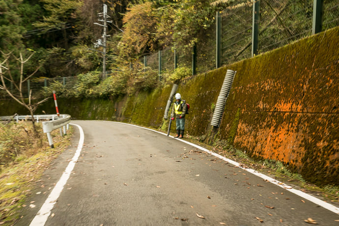 Our Tax Yen at Work worker cleaning middle-of-nowhere street with leaf blower. — what a fantastic waste of resources — taken while riding at 21 kph (13 mph) -- Kyoto, Japan -- Copyright 2015 Jeffrey Friedl, http://regex.info/blog/