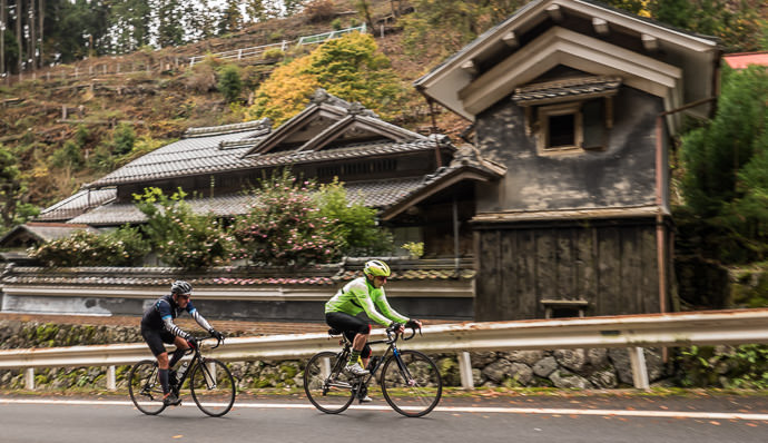 Joshua and Vincent power past an old house; taken while cycling at 12 kph (7 mph) -- Kyoto, Japan -- Copyright 2015 Jeffrey Friedl, http://regex.info/blog/
