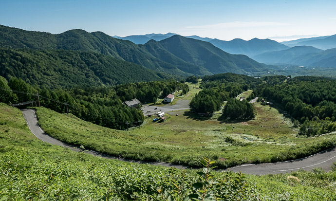 Now On the Norikura Climb Proper looking back to the ski area that marks the start (Mrs. Yoshikawa is on the foreground road, center left) 7:41am - taken while cycling at 9 kph (6 mph) -- Mt. Norikura (乗鞍岳) -- Matsumoto, Nagano, Japan -- Copyright 2016 Jeffrey Friedl, http://regex.info/blog/ -- This photo is licensed to the public under the Creative Commons Attribution-NonCommercial 4.0 International License http://creativecommons.org/licenses/by-nc/4.0/ (non-commercial use is freely allowed if proper attribution is given, including a link back to this page on http://regex.info/ when used online)