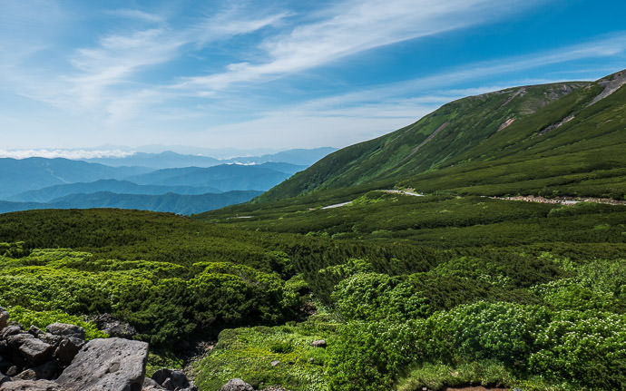 desktop background image of a mountain landscape taken from Mt. Norikura in Japan (乗鞍の景色) -- Find the Leader Mr. Yoshikawa is in this shot somewhere 8:46am - taken while cycling at 11 kph (7 mph) -- Mt. Norikura (乗鞍岳) -- Matsumoto, Nagano, Japan -- Copyright 2016 Jeffrey Friedl, http://regex.info/blog/ -- This photo is licensed to the public under the Creative Commons Attribution-NonCommercial 4.0 International License http://creativecommons.org/licenses/by-nc/4.0/ (non-commercial use is freely allowed if proper attribution is given, including a link back to this page on http://regex.info/ when used online)
