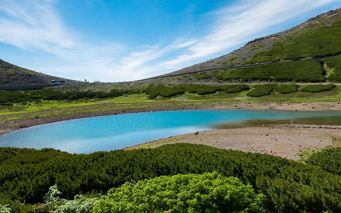 desktop background image of a mountain landscape taken from Mt. Norikura in Japan (乗鞍の景色) -- Volcanic Lake 8:54am - taken while moving at 22 kph (13 mph) -- Mt. Norikura (乗鞍岳) -- Takayama, Gifu, Japan -- Copyright 2016 Jeffrey Friedl, http://regex.info/blog/