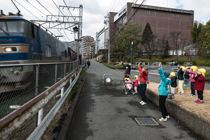 Toddlers Waving to a Train in front of the Suntory Yamazaki Whiskey Distillery -- Yamazaki, Osaka, Japan -- Copyright 2017 Jeffrey Friedl, http://regex.info/blog/ -- This photo is licensed to the public under the Creative Commons Attribution-NonCommercial 4.0 International License http://creativecommons.org/licenses/by-nc/4.0/ (non-commercial use is freely allowed if proper attribution is given, including a link back to this page on http://regex.info/ when used online)