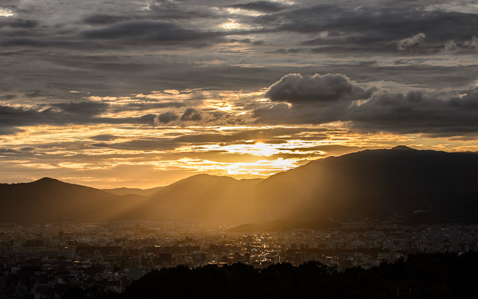 desktop background image of a nice sunset over Kyoto, Japan, from the Shogunzuka (将軍塚) overlook  --  Sun Appears a Bit  --  Shogunzuka (将軍塚)  --  Copyright 2012 Jeffrey Friedl, http://regex.info/blog/