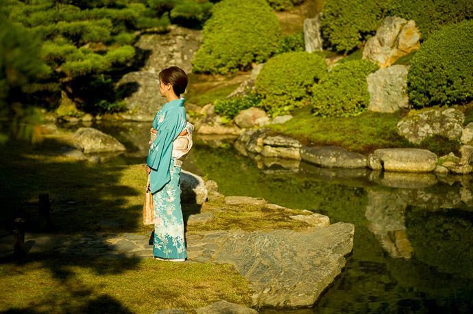 Photo Op in the Garden slightly unbalanced... I tried to will her to turn around, to no avail  --  Shoren'in Temple (青蓮院)  --  Kyoto, Japan  --  Copyright 2012 Jeffrey Friedl, http://regex.info/blog/  --  This photo is licensed to the public under the Creative Commons Attribution-NonCommercial 3.0 Unported License http://creativecommons.org/licenses/by-nc/3.0/ (non-commercial use is freely allowed if proper attribution is given, including a link back to this page on http://regex.info/ when used online)