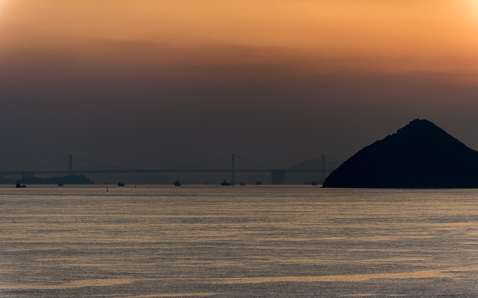 desktop background image of a dusky sunset over Japan  --  The Bridge The Great Seto Bridge, 17km Distant  --  Benesse House  --  Naoshima, Kagawa, Japan  --  Copyright 2012 Jeffrey Friedl, http://regex.info/blog/  --  This photo is licensed to the public under the Creative Commons Attribution-NonCommercial 3.0 Unported License http://creativecommons.org/licenses/by-nc/3.0/ (non-commercial use is freely allowed if proper attribution is given, including a link back to this page on http://regex.info/ when used online)