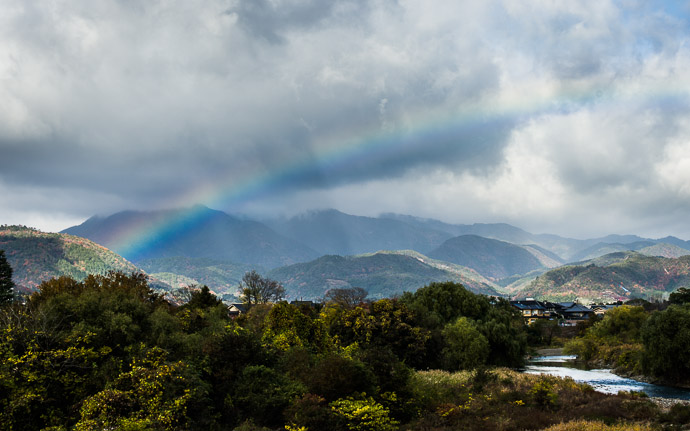 desktop background image of a misty/rainy mountain setting of the Arashiyama (嵐山) area of Kyoto Japan, with a slight rainbow peeking through  --  That Morning Rainbow in Arashiyama (Kyoto Japan) last month  --  Arashiyama (嵐山)  --  Copyright 2012 Jeffrey Friedl, http://regex.info/blog/  --  This photo is licensed to the public under the Creative Commons Attribution-NonCommercial 3.0 Unported License http://creativecommons.org/licenses/by-nc/3.0/ (non-commercial use is freely allowed if proper attribution is given, including a link back to this page on http://regex.info/ when used online)