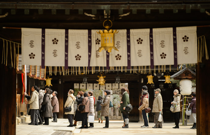 Waiting as seen through a gate with its golden lantern and hanging banners in the foreground -- Kitano Tenmangu Shrine (北野天満宮) -- Kyoto, Japan -- Copyright 2013 Jeffrey Friedl, http://regex.info/blog/ -- This photo is licensed to the public under the Creative Commons Attribution-NonCommercial 3.0 Unported License http://creativecommons.org/licenses/by-nc/3.0/ (non-commercial use is freely allowed if proper attribution is given, including a link back to this page on http://regex.info/ when used online)