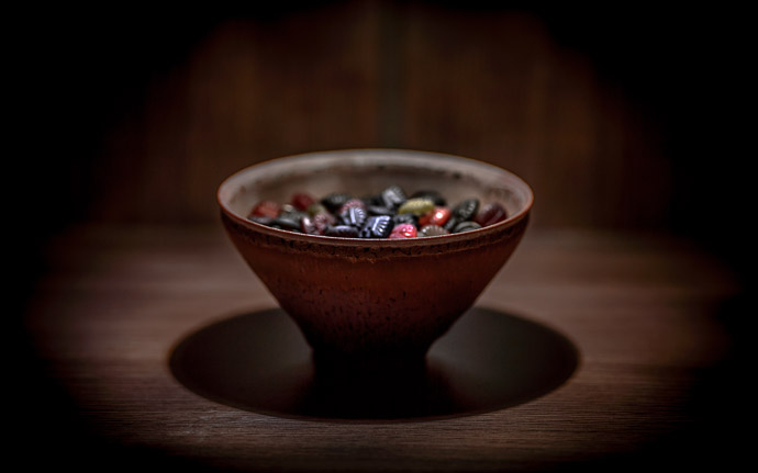 desktop background image of Läkerol candies in a tenmoku pottery bowl by Koji Kamada (鎌田幸二の天目と飴) -- Kyoto, Japan -- Copyright 2013 Jeffrey Friedl, http://regex.info/blog/ -- This photo is licensed to the public under the Creative Commons Attribution-NonCommercial 3.0 Unported License http://creativecommons.org/licenses/by-nc/3.0/ (non-commercial use is freely allowed if proper attribution is given, including a link back to this page on http://regex.info/ when used online)