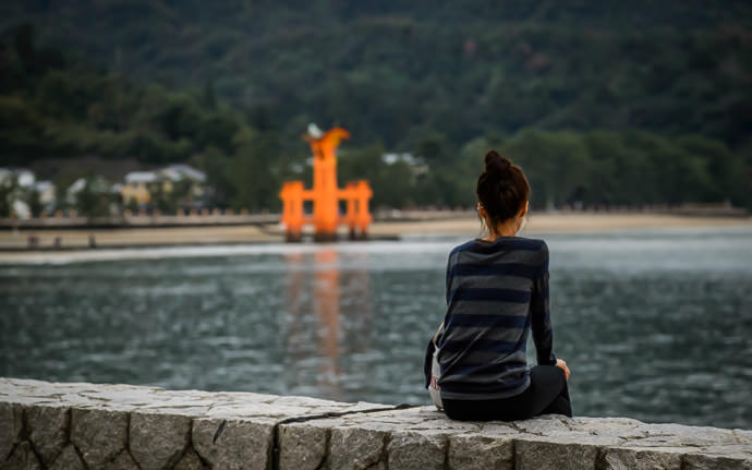 desktop background image of a lady sitting pensively on a seawall in view of the famous gate of the Itsukushima Shrine (厳島神社、宮島) on Miyashima Island, Japan. -- Moment of Solitude Itsukushima Shrine (厳島神社) -- Itsukushima Shrine (厳島神社) -- Miyajima, Hiroshima, Japan -- Copyright 2013 Jeffrey Friedl, http://regex.info/blog/ -- This photo is licensed to the public under the Creative Commons Attribution-NonCommercial 3.0 Unported License http://creativecommons.org/licenses/by-nc/3.0/ (non-commercial use is freely allowed if proper attribution is given, including a link back to this page on http://regex.info/ when used online)
