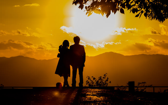 "desktop background image of a couple silhouetted against an orange sunset, at the Shogunzuka Overlook, Kyoto Japan (将軍塚、京都市) -- "" There's the Sun "" -- Shogunzuka Overlook (将軍塚) -- Copyright 2013 Jeffrey Friedl, http://regex.info/blog/ -- This photo is licensed to the public under the Creative Commons Attribution-NonCommercial 3.0 Unported License http://creativecommons.org/licenses/by-nc/3.0/ (non-commercial use is freely allowed if proper attribution is given, including a link back to this page on http://regex.info/ when used online)"