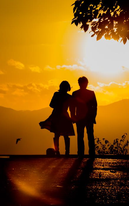 desktop background image of a couple silhouetted against an orange sunset, at the Shogunzuka Overlook, Kyoto Japan (将軍塚、京都市) -- Brisk Wind -- Shogunzuka Overlook (将軍塚) -- Copyright 2013 Jeffrey Friedl, http://regex.info/blog/ -- This photo is licensed to the public under the Creative Commons Attribution-NonCommercial 3.0 Unported License http://creativecommons.org/licenses/by-nc/3.0/ (non-commercial use is freely allowed if proper attribution is given, including a link back to this page on http://regex.info/ when used online)