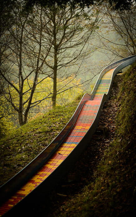 desktop background image of roller-slide down a hill at Yamabiko-no-Mori in Takatsuki, Japan (山びこの森、大阪府高槻市) -- For a Quick and Colorful Descent 山びこの森 Mountains of northern Takatsuki, Japan -- Takatsuki, Osaka, Japan -- Copyright 2013 Jeffrey Friedl, http://regex.info/blog/ -- This photo is licensed to the public under the Creative Commons Attribution-NonCommercial 3.0 Unported License http://creativecommons.org/licenses/by-nc/3.0/ (non-commercial use is freely allowed if proper attribution is given, including a link back to this page on http://regex.info/ when used online)