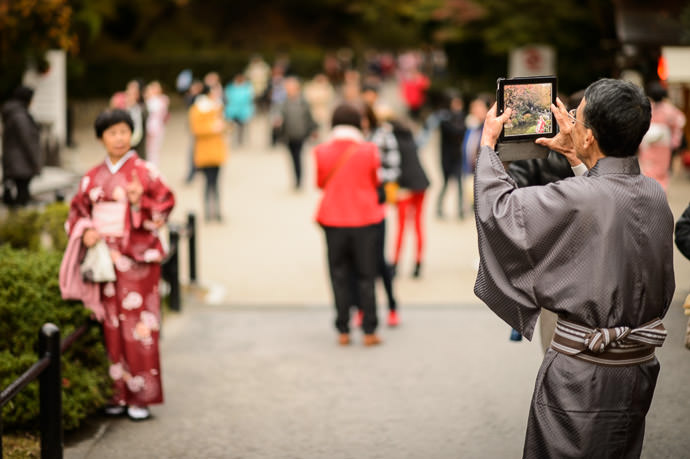 an elderly man in traditional Japanese kimono uses an iPad to photograph an elderly woman (presumably his wife) also in traditional Japanese kimono, at the Kiyomizu Temple (清水寺), Kyoto Japan