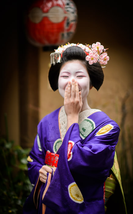 desktop background image of a young Japanese women, dressed in full regalia of a maiko (apprentice geisha), in Kyoto Japan -- Laughing because I said something funny -- Gion -- Copyright 2014 Jeffrey Friedl, http://regex.info/blog/
