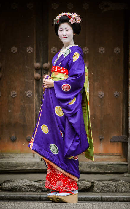 desktop background image of a young Japanese women, dressed in full regalia of a maiko (apprentice geisha), in Kyoto Japan -- Posing Here... -- Gion -- Copyright 2014 Jeffrey Friedl, http://regex.info/blog/