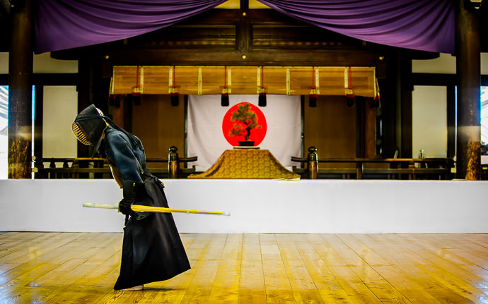 desktop background image of a kendo (Japanese fencing) master after a bout in Kyoto, Japan (剣道士,京都市) -- Parting Bow a kendo master prepares to depart the dojo after a bout -- Kyubutokuden (旧武徳殿) -- Copyright 2014 Jeffrey Friedl, http://regex.info/blog/ -- This photo is licensed to the public under the Creative Commons Attribution-NonCommercial 4.0 International License http://creativecommons.org/licenses/by-nc/4.0/ (non-commercial use is freely allowed if proper attribution is given, including a link back to this page on http://regex.info/ when used online)