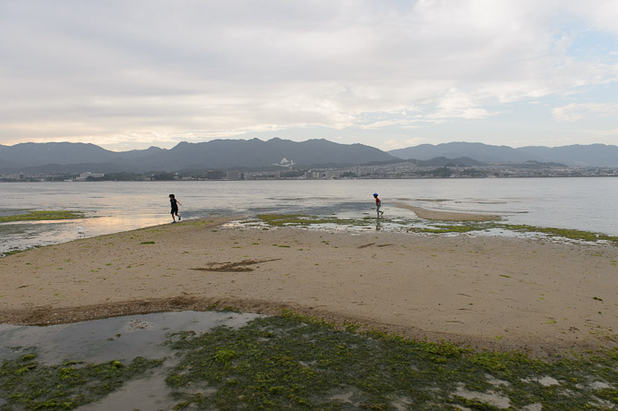 Kids Playing at Low Tide in a few hours, the water will be four times their height -- Miyajima, Hiroshima, Japan -- Copyright 2014 Jeffrey Friedl, http://regex.info/blog/ -- This photo is licensed to the public under the Creative Commons Attribution-NonCommercial 4.0 International License http://creativecommons.org/licenses/by-nc/4.0/ (non-commercial use is freely allowed if proper attribution is given, including a link back to this page on http://regex.info/ when used online)