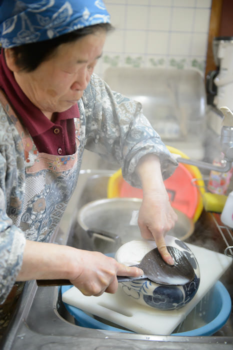 Squeezing Out Remaining Soy Milk using the same spatula she's used for 58 years (she's using the spatula instead of her hands because the stuff is really hot ) -- Takashima, Shiga, Japan -- Copyright 2015 Jeffrey Friedl, http://regex.info/blog/
