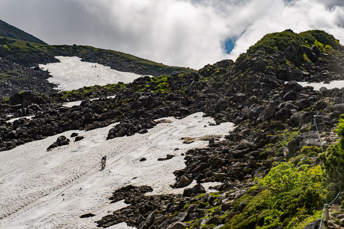 Small Spot of Snow with one person climbing it (the spot in the back has four people on it) -- Mt. Norikura (乗鞍岳) -- Matsumoto, Nagano, Japan -- Copyright 2016 Jeffrey Friedl, http://regex.info/blog/ -- This photo is licensed to the public under the Creative Commons Attribution-NonCommercial 4.0 International License http://creativecommons.org/licenses/by-nc/4.0/ (non-commercial use is freely allowed if proper attribution is given, including a link back to this page on http://regex.info/ when used online)