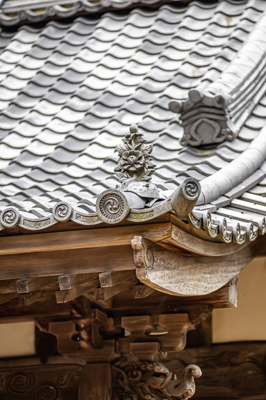Detail in both the roof tiles and eave woodwork -- Kotoku-ji Temple (庚申山広徳寺) -- Japan, Shiga, Koka -- Copyright 2019 Jeffrey Friedl, http://regex.info/blog/ -- This photo is licensed to the public under the Creative Commons Attribution-NonCommercial 4.0 International License http://creativecommons.org/licenses/by-nc/4.0/ (non-commercial use is freely allowed if proper attribution is given, including a link back to this page on http://regex.info/ when used online)