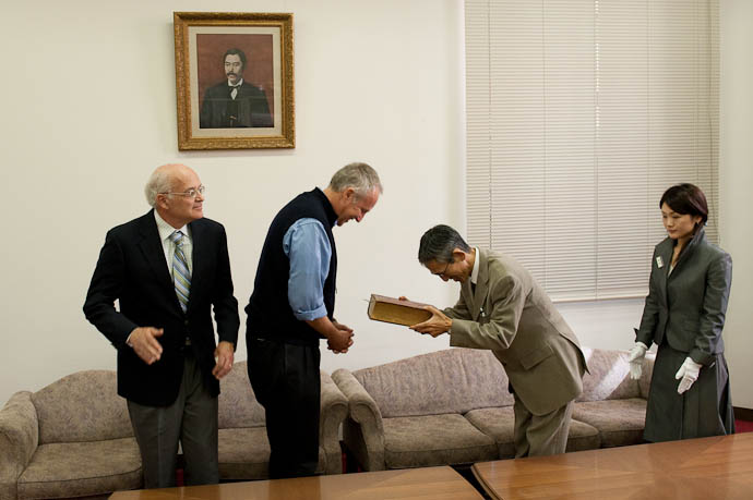 Archive Director Prof. Takuya Tsuyuguchi Accepts the Bible as the white-gloved archivist awaits, and John Brigham, another great-great-grandson, looks on -- Kyoto, Japan -- Copyright 2008 Jeffrey Friedl, http://regex.info/blog/
