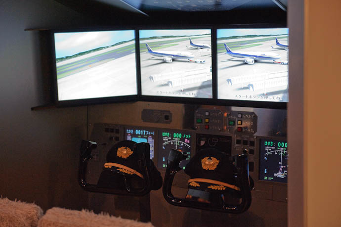 Cockpit Simulator with pilot hats waiting for kids -- KidZania Koshien -- Kyoto, Japan -- Copyright 2009 Jeffrey Friedl, http://regex.info/blog/