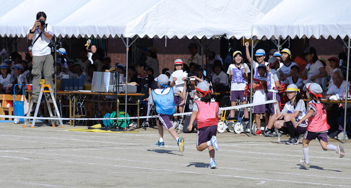 Breaking the Tape winning his heat of six runners, scoring a point for the blue team -- Kyoto, Japan -- Copyright 2009 Jeffrey Friedl, http://regex.info/blog/