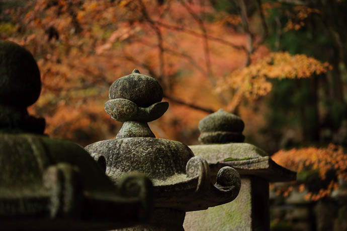 desktop background image of the tops of three old stone lanterns in Kyoto Japan, against a backdrop of bright orange fall foliage. -- Three Crowns -- Nishimura Stone Lantern workworkshopshop and garden -- Copyright 2009 Jeffrey Friedl, http://regex.info/blog/