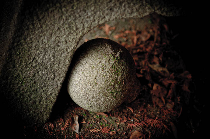desktop background image of a stone sphere, tucked away haphazzardly under the legs of a stone lantern, in the back gardens of the Nishimura Stone Lantern stonecarving shop, Kyoto Japan -- Sphere -- Nishimura Stone Lantern workworkshopshop and garden -- Copyright 2009 Jeffrey Friedl, http://regex.info/blog/