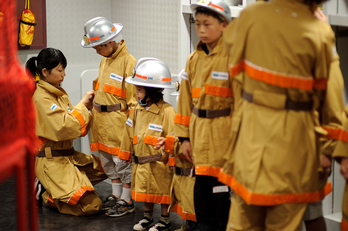 Helping Hand the little girl next to Anthony is tooooooo cute with that big helmet, thick chinstrap, long coat, and little shoes -- KidZania -- Nishinomiya, Hyogo, Japan -- Copyright 2010 Jeffrey Friedl, http://regex.info/blog/