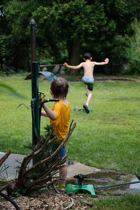 """Get You!"" Game Josh controls the sprinkler water to try to ""get"" Anthony -- Rootstown, OH, USA -- Copyright 2010 Jeffrey Friedl, http://regex.info/blog/"