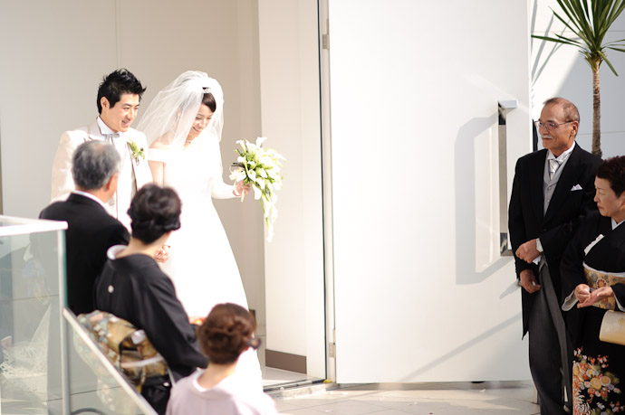 Shogo and Namiko emerge from the chapel ( with his folks waiting at left, her folks at right ) -- Wedding of Shogo and Namiko -- Nagoya, Aichi, Japan -- Copyright 2010 Jeffrey Friedl, http://regex.info/blog/