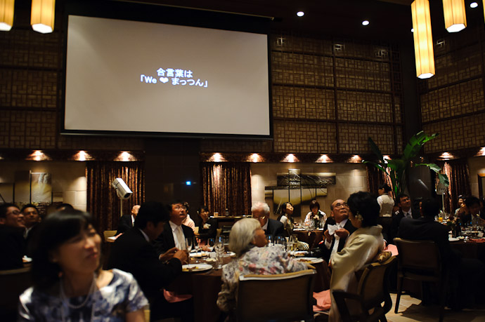 Motto: We ♥ まっつん ( there were video screens on opposing walls ) -- Wedding of Shogo and Namiko -- Nagoya, Aichi, Japan -- Copyright 2010 Jeffrey Friedl, http://regex.info/blog/