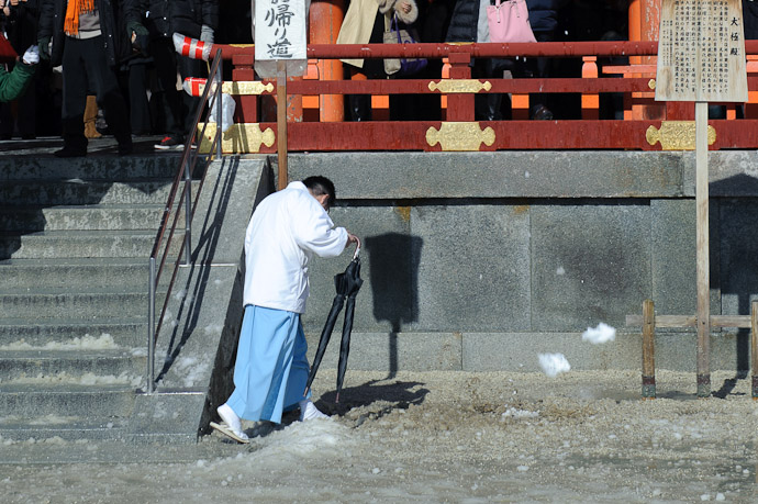 Splat two small hunks of snow caught mid-air to the right of the worker following a bunch that had already splatted moments before -- Heian Shrine -- Kyoto, Japan -- Copyright 2011 Jeffrey Friedl, http://regex.info/blog/