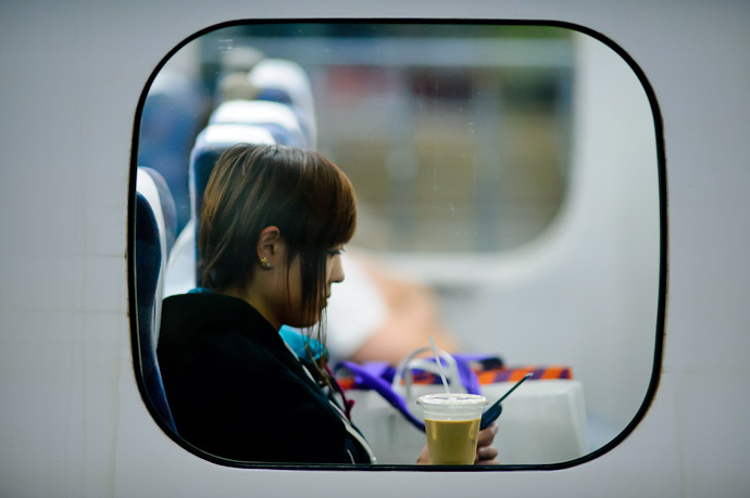 Quality Time girl in a train on the opposite tracks -- Kyoto Station (京都駅) -- Kyoto, Japan -- Copyright 2011 Jeffrey Friedl, http://regex.info/blog/