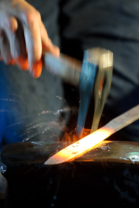 desktop background image of glowing-hot metal being hammered into a knife -- Pierre Nadeau's Smithy -- Aridagawa, Wakayama, Japan -- Copyright 2011 Jeffrey Friedl, http://regex.info/blog/