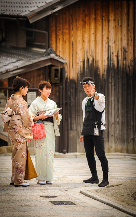 desktop background image of a ricksha driver giving directions to two ladies in kimono, in Kyoto Japan  --  Neighborly Assistance  --  Copyright 2012 Jeffrey Friedl, http://regex.info/blog/