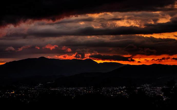 desktop background image of a dynamic sunset over Kyoto, Japan, as seen from the Shogunzuka overlook (将軍塚からの京都の夕焼け)  --  Night Settles on Kyoto The Sun (and typhoon #4) say goodnight  --  Shogunzuka (将軍塚)  --  Copyright 2012 Jeffrey Friedl, http://regex.info/blog/
