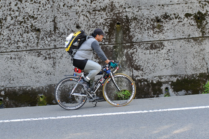 Interesting 3:04pm - interesting that he bothered with a reflective ankle bracelet, but no helmet -- Otsu, Shiga, Japan -- Copyright 2015 Jeffrey Friedl, http://regex.info/blog/